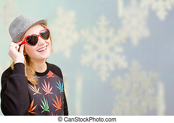 Beautiful lady in sunglasses and hat on digital winter background