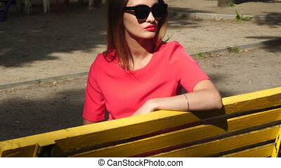 beautiful lady in sunglasses and red suit sits on a yellow bench at the park