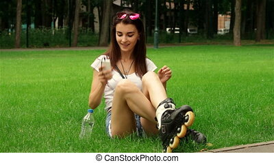 beautiful lady listens to music and sitting on the grass in rollers