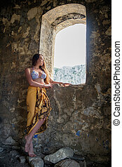 Beautiful lady posing among antique ruins