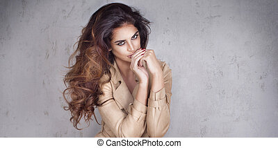 Beautiful lady with long curly hairstyle posing.