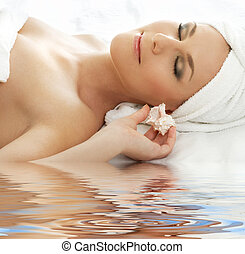 beautiful lady with sea shell in spa