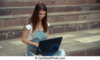 beautiful lady with the laptop sitting on the stairs outdoors