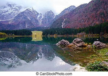 Beautiful Lago di Fusine mountain lake in autumn and Mangart mountain in the background at sunset