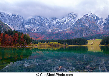 Beautiful Lago di Fusine mountain lake in autumn and Mangart...