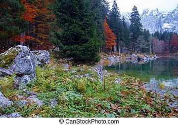Beautiful Lago di Fusine mountain lake in autumn and Mangart...