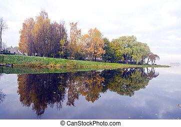 Beautiful lake and autumn trees reflect on water.