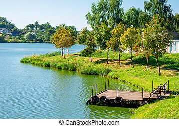 beautiful lake and wooden pier in a summer day