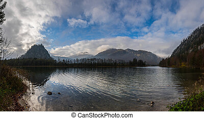 beautiful lake in the mountains with clouds on the sky panorama view