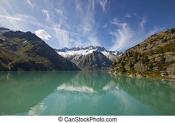 beautiful lake on the Goescheneralp with snow covered mountains in the background