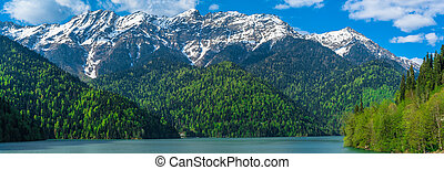 Beautiful Lake Ritsa in the Caucasus Mountains. Green mountain hills, blue sky with clouds. Spring landscape panorama