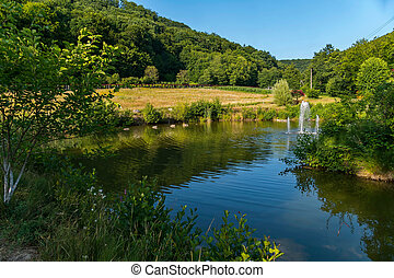 beautiful lake with a fountain and gazebo on the background of green mountains