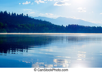 Beautiful lake with mountains in the background at sunrise.
