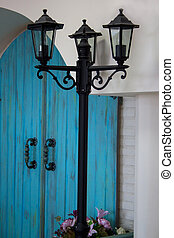 Beautiful lamppost is standing in front of the house with an arch.
