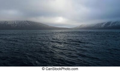 Beautiful landscape blue sea and cloudy sky on snowy...