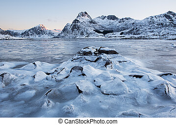 Beautiful landscape cracking ice, frozen sea coast with mountain ridge background at sunrise in winter season, Lofoten Islands, Norway