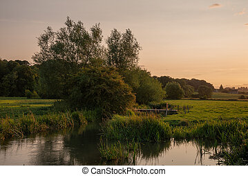 Beautiful landscape image of Burford village in English Cotswolds countryside during Summer evening