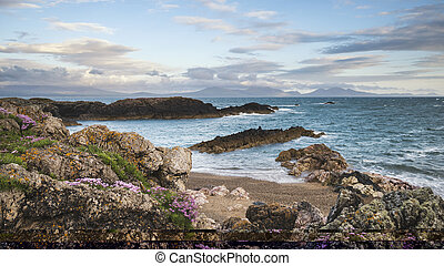 Beautiful landscape image of rocky beach with Snowdonia mountain range in background at sunset