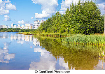 Beautiful landscape of a small lake and city. Light wind on the lake. Clouds are reflected in the water