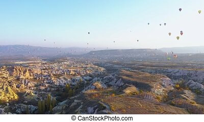 Beautiful landscape of Cappadocia. Panorama of flying hot air balloons and rock landscape at sunset. Picturesque scene from above.