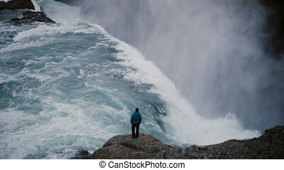 Beautiful landscape of Gullfoss waterfall. Back view of man standing on the edge of the rock and enjoying the view.
