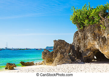 Beautiful landscape of tropical beach, rocks with vegetation, sea and white sand. Summer vacation concept.