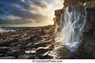 Beautiful landscape waterfall flowing into rocks on beach at sunset