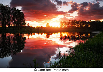 Beautiful landscape with fiery sunset over the lake. View from the coast