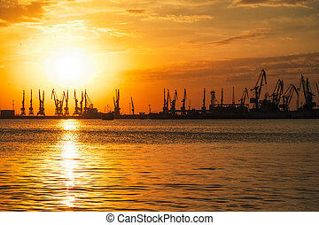 Beautiful landscape with fiery sunset sky and sea. Harbor on the coast during sunrise. Cranes silhouettes against fiery, orange and red sky.
