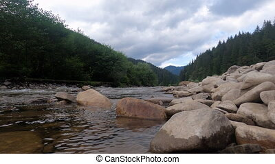 Beautiful landscape with mountain river and forest, stones in the foreground
