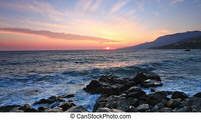 Beautiful landscape with sunrise over the sea and rocks