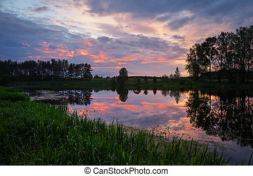 Beautiful landscape with sunset sky over the lake. View from the coast