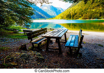 Beautiful landscape. Wooden bench overlooking the lake and mountains.