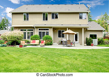 Beautiful large house with backyard with sitting area and umbrella.