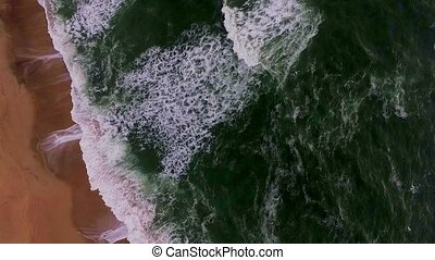 Beautiful large waves arrive on the sandy beach of Africa....