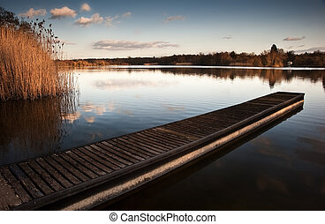Beautiful late evening sunset landscape over jetty on lake
