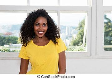 Beautiful latin american young adult woman looking at camera...