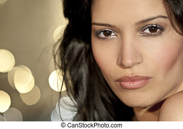 A stunningly beautiful young Latina Hispanic woman looking sultry shot in front of sparkling city lights