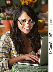 Beautiful Latina Woman at table in Kitchen with Computer