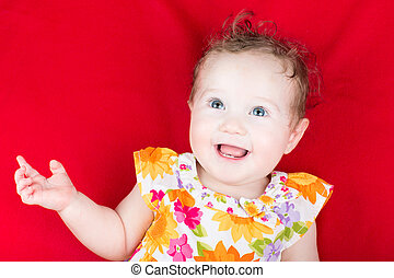 Beautiful laughing baby girl in a floral dress