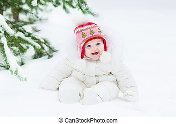Beautiful laughing baby girl sitting under a Christmas tree wear
