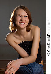 laughing girl in black corset and blue jeans