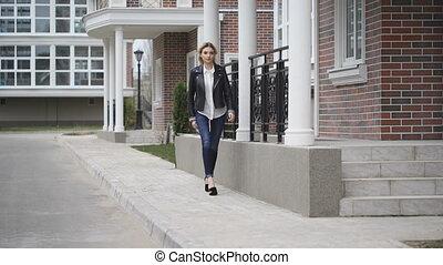 Beautiful leggy blonde confident gait walking down the street. Black leather jacket,