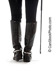 beautiful legs in black leather horseman boots with riding-crop over white