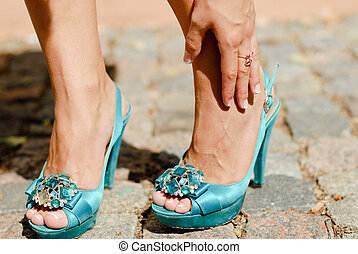 Beautiful legs in blue high heel shoes and hand touching ankle in pain