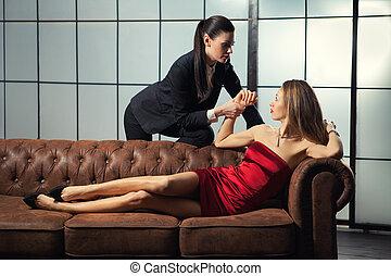 Beautiful lesbian flirting couple on the sofa.