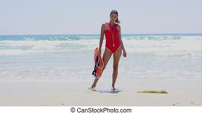 Beautiful lifeguard wearing red swim suit stands with rescue can near pounding ocean