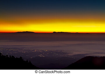 eautiful light behind the mountain in the morning time with the Drifting fog above the city between two mountain at from a Doi Ang Khang, Chiang Mai, Thailand