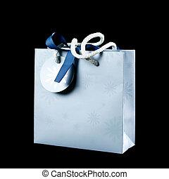 Beautiful light blue gift bag. Close up. Isolated on black background