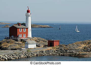 Lighthouse on the rocks on the background of the ocean